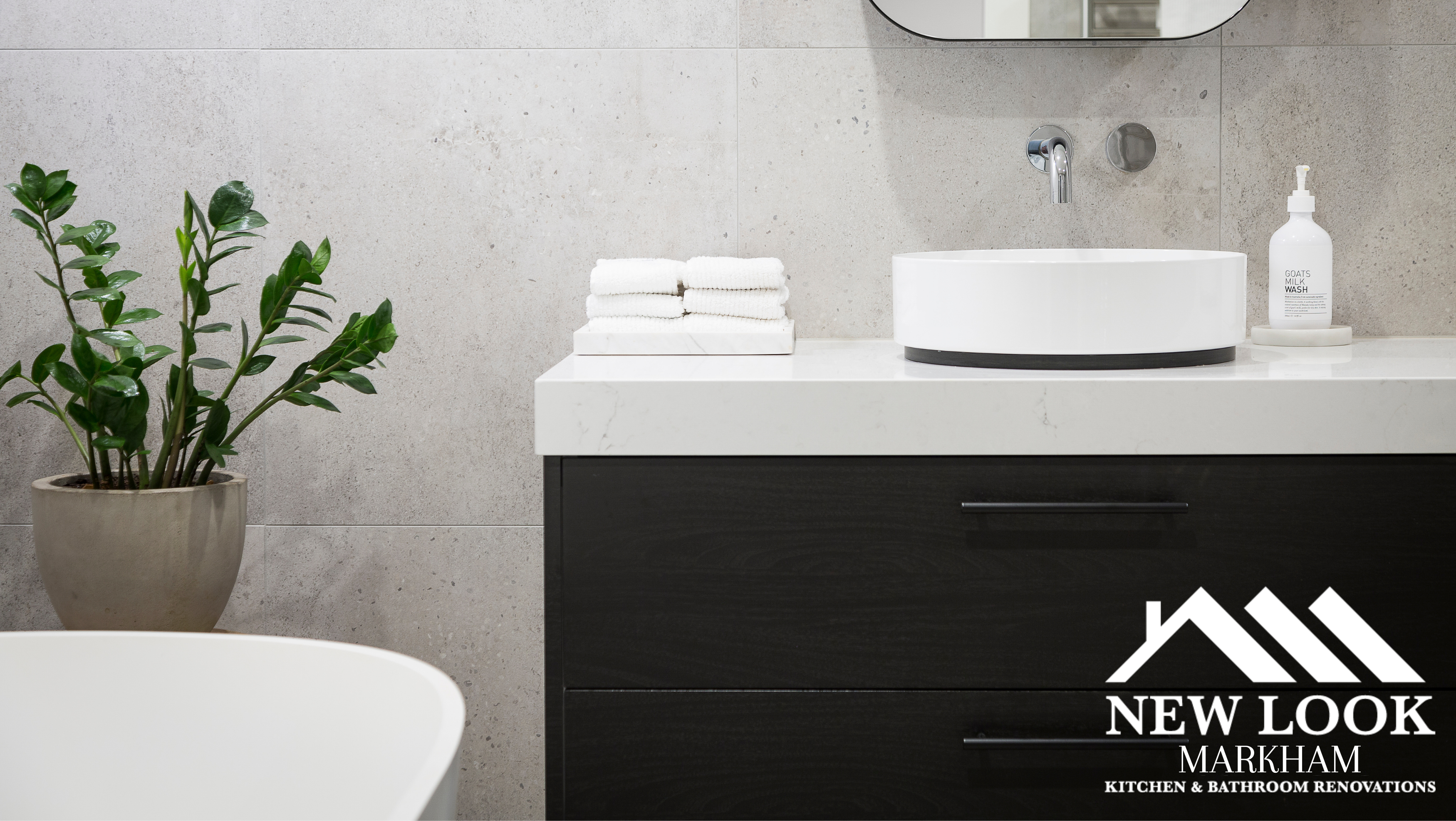 Black bathroom vanity with white countertop, white sink, white modern bathtub, and a green house plant.